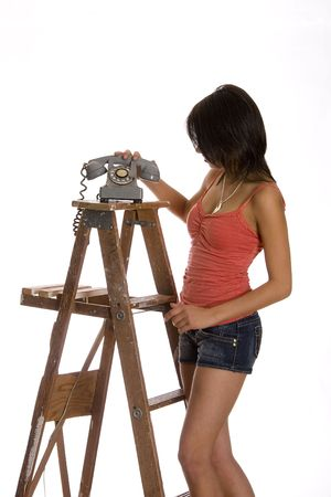 teenage girl standing on ladder about the anwser phone