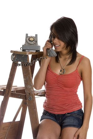 teenage girl standing on ladder talking on a old rotary phone photo