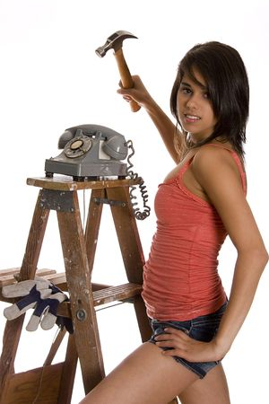 teenage girl standing on ladder about to smash old rotary phone with a hammer photo