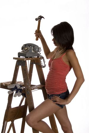 teenage girl standing on ladder about to smash old rotary phone with a hammer