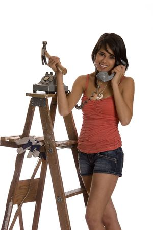 teenage girl standing on ladder talking old rotary phone with a hammer in her hand