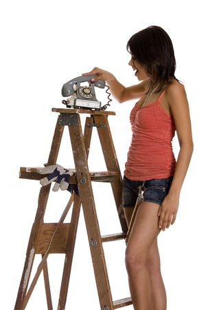 teenage girl standing on ladder slamming an old rotary phone  Banco de Imagens