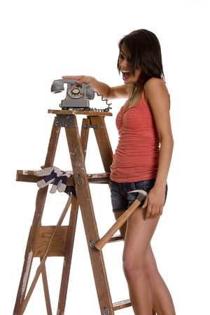 teenage girl standing on ladder screaming while slamming an old rotary phone