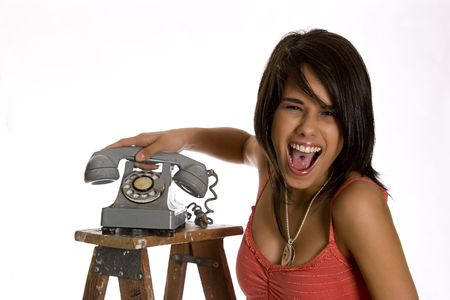 screaming mad teenage girl standing on ladder slamming an old rotary phone