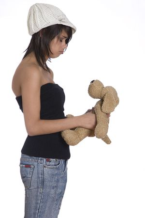 tube top: Teenage girl wearing a black tube top, knitted hat and jeans with holes holding a brown stuff dog plush toy with sad expression