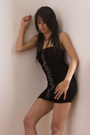 Teenager girl in little black dress leaning against a corner wall photo