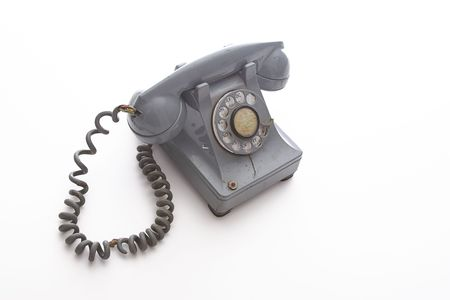 dirty vintage gray rotary phone with crack casing and expose wired