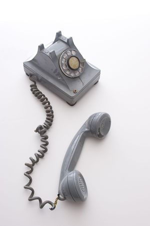 earpiece: dirty vintage gray rotary phone with crack casing and expose wired, unhooked and left there