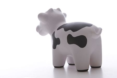 small black and white toy cow against white background viewed from behind Stock Photo