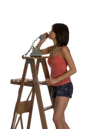 teenage girl standing on ladder talking on a old rotary phone Banco de Imagens