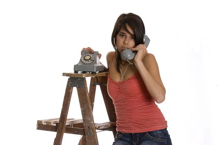 teenage girl standing on ladder talking on a old rotary phone with annoyed expression Banco de Imagens