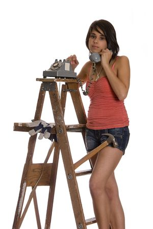 teenage girl standing on ladder talking on a old rotary phone with