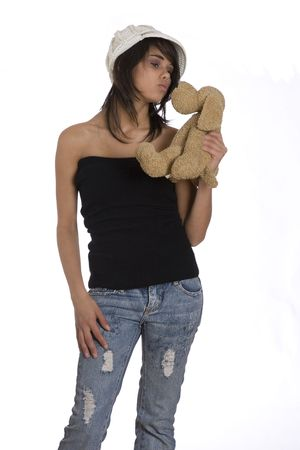 tube top: Teenage girl wearing a black tube top, knitted hat and jeans with holes about to kiss brown stuff dog plush toy