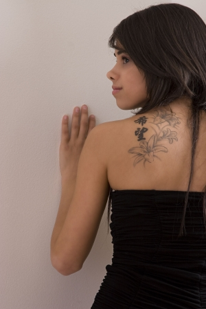 Teen girl in little black dress showing the chinese inspired flower tatoo on her back photo