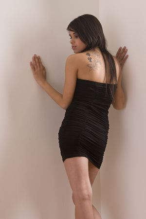 tight dress: Teen girl in little black dress showing the chinese inspired flower tatoo on her back Stock Photo