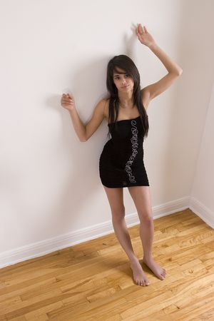 Teenager girl in little black dress leaning against wall while barefoot photo