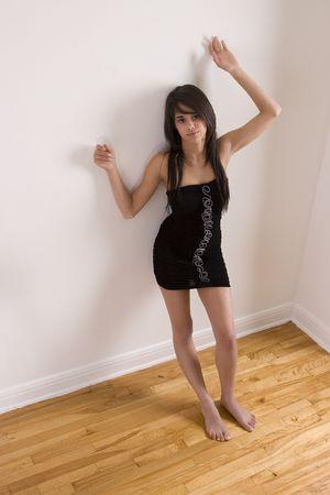 Tiener meisje in little black dress leunend tegen muur terwijl barefoot