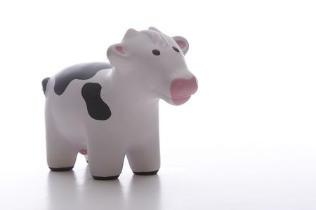 small black and white toy cow against white background