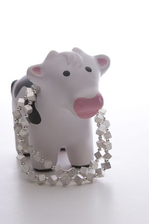 small black and white toy cow against white background wearing a silver necklace