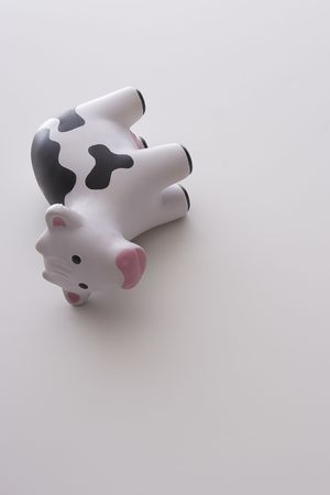 small black and white toy cow against white background tipped on its side Stock Photo