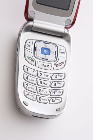 wireles: close up on the keypad of a red and silver cellular phone open with a blank screen Stock Photo
