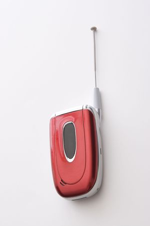 wireles: Red, black and silver cellular phone with extended antenna