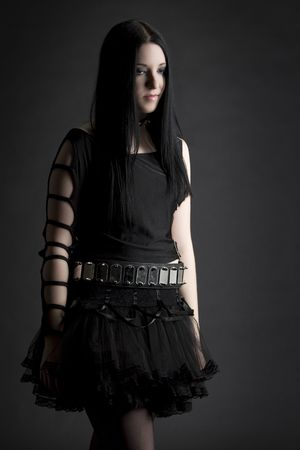 teen girl with black hair and goth style with depress expression wearing a black tutu