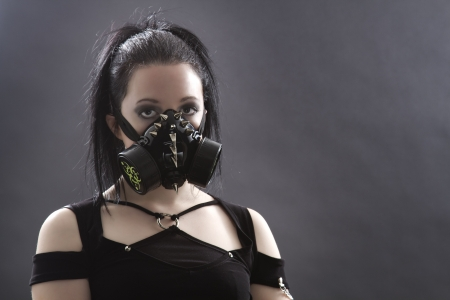 head shot of a teenage girl with black hair and a gas mask photo