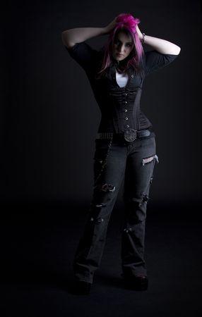 Fille Goth avec des cheveux rose et corps perçage tenant ses cheveux noir et Rose