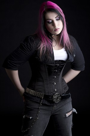 rebels: Goth girl with pink hair and body piercing with her hands in the back pocket of her black jeans Stock Photo