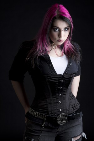 Goth girl avec des cheveux Rose et du piercing avec ses mains dans la poche arrière de son jeans noirs