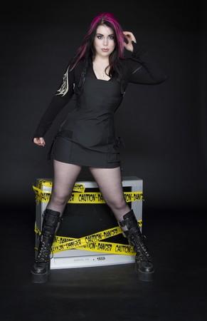 adolescente porte gothique inspiré des vêtements avec des cheveux rose et noir de devant une tv en tenant une broche de pose
