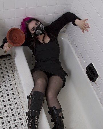 crazy looking teenage girl wearing goth inspired clothes with pink and black hair and gas mask in a tub with a plunger in her hand photo