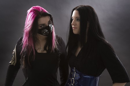 crazy looking teenage girls wearing goth inspired clothes with pink, black hair and gas mask