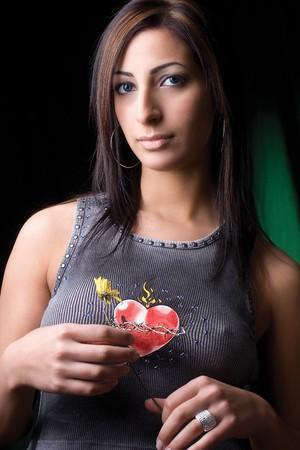 Twenty something fashion model with rocker attitude holding a flower photo