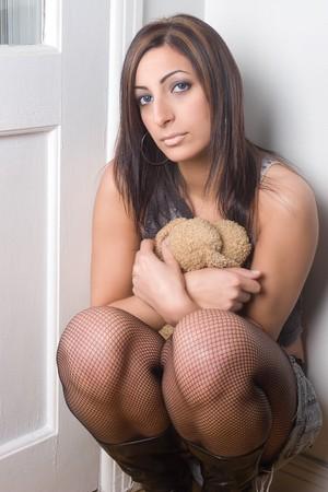 depress: Twenty something fashion model crouching in a corner with a depress expression huggy a teddy bear