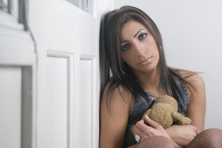 Twenty something fashion model with teddy bear in hand looking sad photo