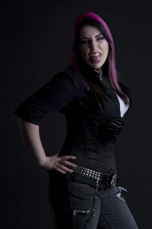 Goth girl avec des cheveux Rose et lancer sa langue en colère et montrant sa langue du piercing perçage