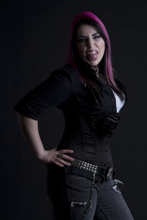 Goth girl with pink hair and body piercing throwing her tongue in anger and showing her tongue piercing