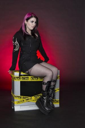 adolescente portant goth inspiré des vêtements avec des cheveux Rose et noir, assis sur un téléviseur avec un brut expression Banque d'images