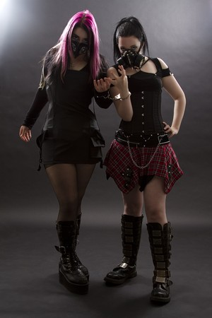 teenage girls wearing goth inspired clothes with pink, black hair and gas mask, shackle together by handcuffs photo
