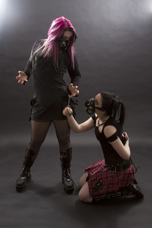 crazy looking teenage girl wearing goth inspired clothes with pink and black hair and gas mask in mistress and slave position handcuff to one another Standard-Bild