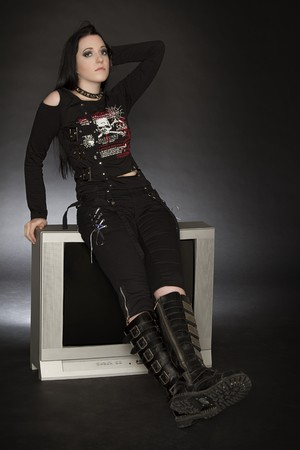 Teenage girl in goth style clothes sitting on a tv 免版税图像