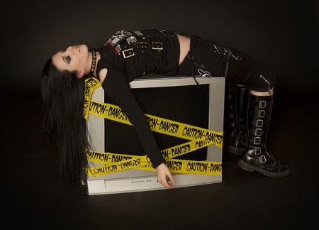 Teenage girl in goth style clothes laying on a television