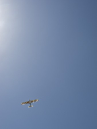 Ultralight aircraft flying over against a blue sky