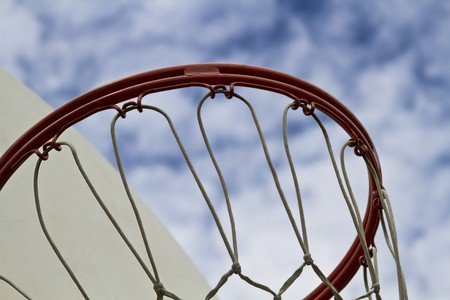 Close up shoot of a basketball hoop against a clouded blue sky Stockfoto