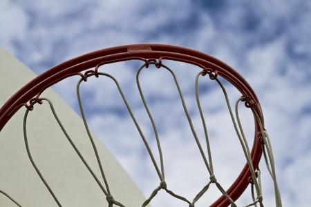 Close up shoot of a basketball hoop against a clouded blue sky Banco de Imagens