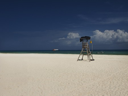 Caribbean beach with empty lifeguard chair and boat in the distance photo