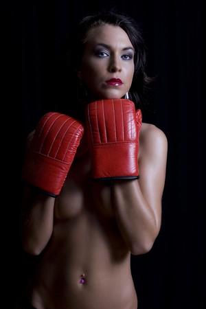 Twenty something women holding her breast with boxing glove Stock Photo