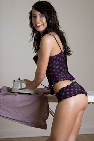 young twenty something women in pokedot lingerie ironing a man shirt photo